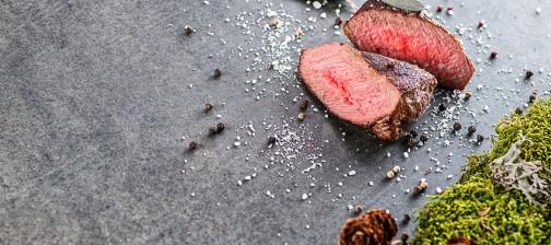 deer or venison steak with ingredients like sea salt, herbs and pepper, food background for restaurant or hunting loving